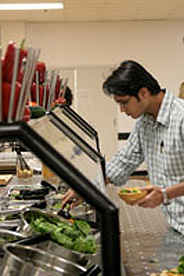 A student selecting meal from options in the cafeteria.