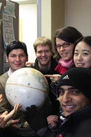International students pointing to home countries on a globe.