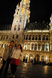 Students in front of city buildings lit up at night