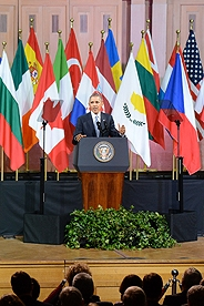President Obama speaking in front of world flags.