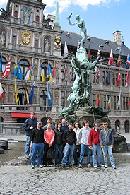 Students stand in front of a fountain in a Brussels square.