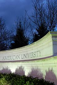 American University sign illuminated at night with lights against a dark sky