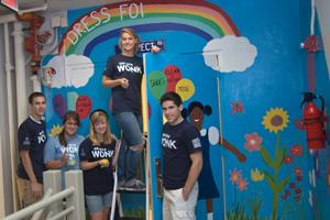 AU students painting a mural as part of their volunteer service with a local DC non-profit.