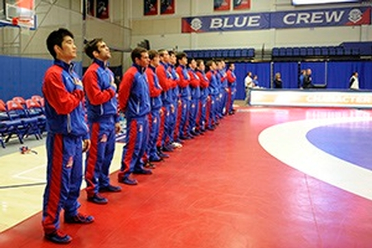 The American University men's wrestling team stands with their hands over their hearts as the national anthem plays before a match in Bender Arena.