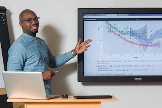 Data scientist standing in front of screen with data.