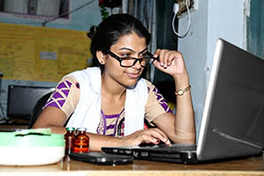 A young South Asian woman works at her laptop.