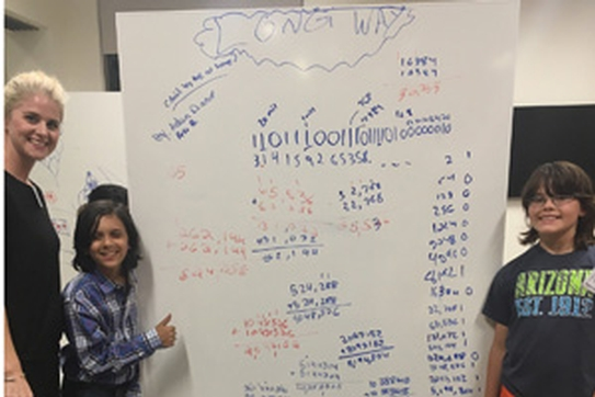 Math professor Jaime Miller with two students in front of a white board with math problems.