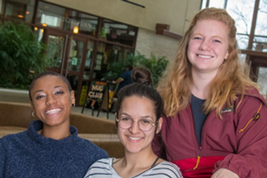Three student sustainability educators. Faith Lewis (left), Matilda Kitabwalla, and Danielle Smith. Sitting in the atrium of the School of International Service.