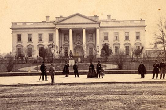 The North Grounds of the White House. Several people walking outside the greenery. Circa 1860s. Photo provided by the White House Historical Association.