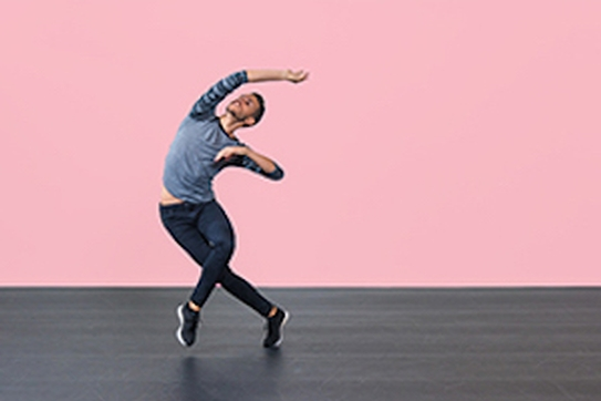 Male dancer on stage in front of pink background.