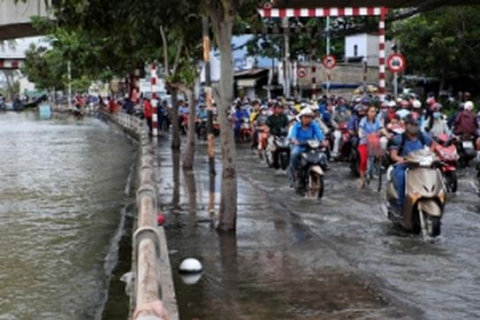 People ride motorcycles through a flooded street in Ho Chi Minh, Vietnam