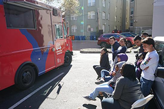 a group of young students stand in front of the red Humanities Truck