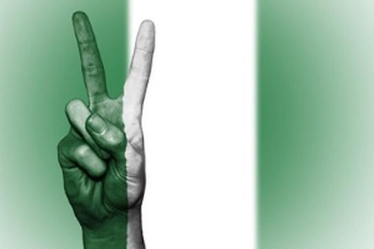 Peace sign in front of the Nigerian flag