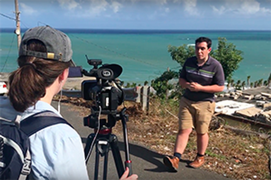 Two students film for their journalism class in front of the ocean in Puerto Rico