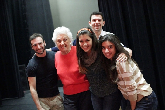 A smiling group of students poses backstage with arms around Mrs. Greenberg