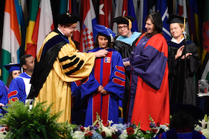 Anila (middle) is hooded during graduation by her mentor Stoodley (right).