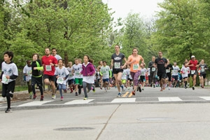 Dozens of participants run along the road of the WPI 5K Race.