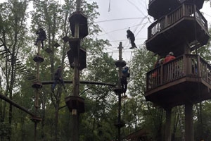 Students soar through the sky at a ropes course as part of the leadership retreat.