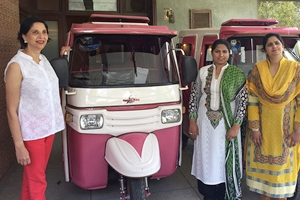Zar Aslam and Sara Naseem standing next to pink rickshaws for PWEP.