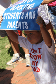Photo of child holding a sign in protest against deportation policies. Sign reads,