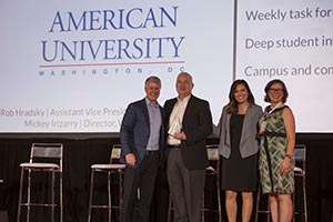 Robert Hradsky and Mickey Irizarry (middle two) accept the EVERFI award on AU's behalf.