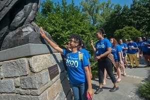 A photo of an African-American female student who is a member of AU's class of 2020.  She is touching the talons of the eagle statue for good luck.