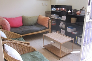 image of the au nairobi center student lounge with a rattan couch and chair, pillows, a filled book case and a coffee table
