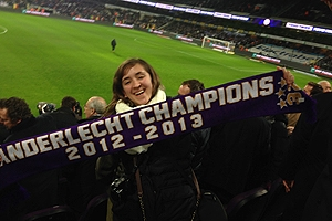 A student holds a soccer scarf up at a match