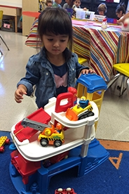 Little girl playing with a colorful toy car in a classroom