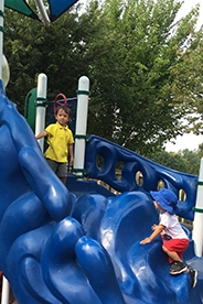 Children on a large blue slide at a playground