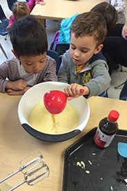 Child pours liquid in a mixing bowl while the other child sitting next to him watches.