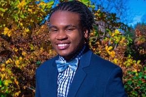 Photo of Jjayi in navy jacket and bowtie.