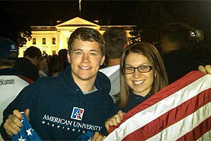 students hold an American flag outside the White House at night