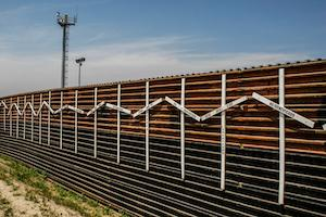 US Mexico border wall streching out beneath blue sky