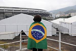 A woman draped in the Brazilian flag watches temporary hospital installation in Rio de Janeiro