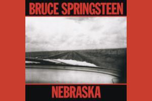 Cover art from Bruce Springsteen's album Nebraska; A car dashboard driving down a lonely road between empty fields; Black and white