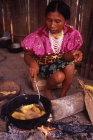 Indigenous woman cooking over an open fire