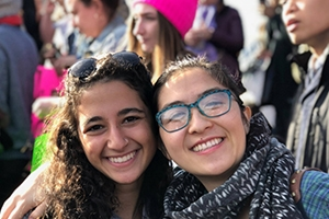 Christine Miyashiro (right) and fellow AU student Maia Banayan at the 2018 Women's March, standing in front of crowd.