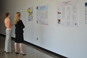 Photo: Two people look at poster displays at the 20th-annual Robyn Rafferty Mathias Research Conference.