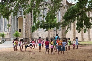 A group of children play outside a church