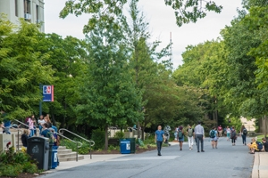 On campus with people walking, trees, and an AU flag.