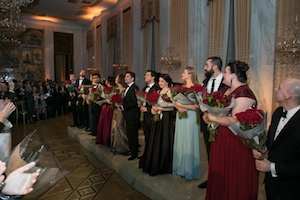 Performers stand in front of audience holding flowers at the Russian Embassy