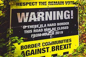 A Border Communities Against Brexit sign on the side of a road.