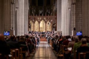 An audience watches an orchestra in pews at a traditional looking cathedral.