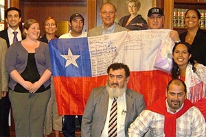 Chilean miners pose with Dean Claudio Grossman and the flag they presented to him signed by all 33 rescued miners.