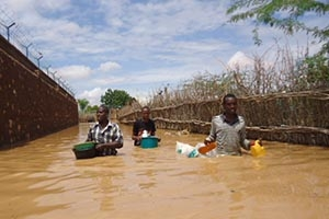 Three men wade through mirky water in Beletweyne while they carry water jugs.