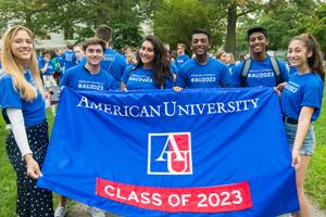 Students wearing blue shirts, holding banner