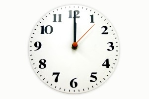 A white wall clock with the arms at twelve o clock