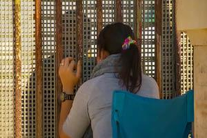 A woman looks at a figure through a gate.