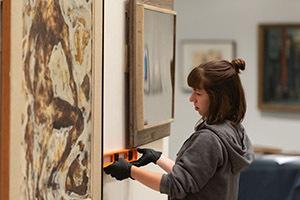 A person measures two art pieces on the wall at the AU museum.